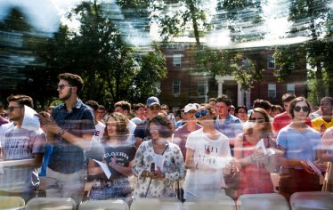 students stand and clap at Tufts' matriculation exercises