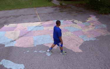 still from the film showing a young boy walking past a chalk map of the U.S. on a playground