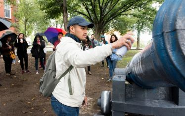 Timothy Manalo spray paints the Tufts cannon