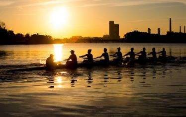 women's crew team on the river at sunrise