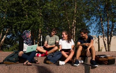 students sit and talk on Tufts' Medford/Somerville campus