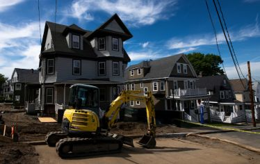 A backhoe in front of one of the Community Housing—or CoHo—project homes, new residences for juniors and seniors at Tufts, one of the many construction projects under way at the university this summer.