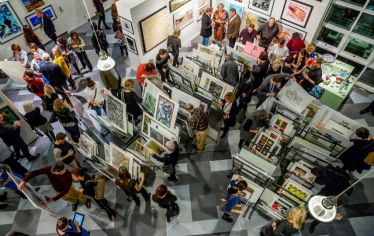 View from above of people looking at art for sale. The SMFA Art Sale helps artists while also raising needed funds to provide financial aid to deserving students and support faculty.