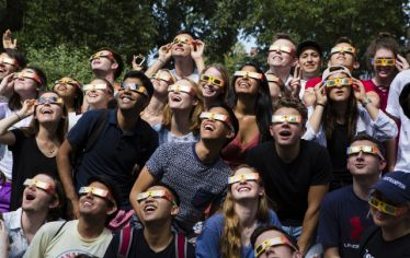 Young people with special glasses look upwards at the sky. The top Tufts photos of the decade 2010-2019.