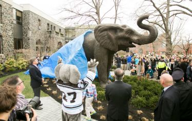 A tarp half covers a big elephant statue, with people surrounding it. Campus milestones at Tufts for 2010-2019 are shown in eleven photographs.