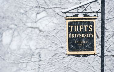 Snow falls on a sign for Tufts University.