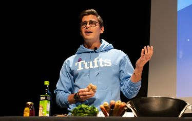 Antoni Porowski, the food and wine specialist from the Netflix show Queer Eye, preparing a salad on stage at Tufts University. A sold-out crowd of undergrad students packed the auditorium to ask questions of the lifestyle expert.