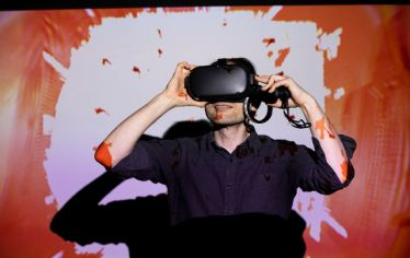 A man with a VR headset covering his eyes, against a screen with orange coloring. A School of the Museum of Fine Arts professor and his students talk about the vast potential of VR