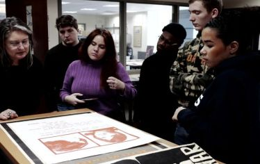 A professor and her students look at a poster depicting two students killed in the 1970 Kent State shootings. Their visit to the Tufts archives was part of a course at the School of the Museum of Fine Arts at Tufts.