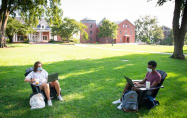 Two students sit in chairs on the academic quad. The first day of undergraduate classes looked very different this year, but students were still excited to be back on campus