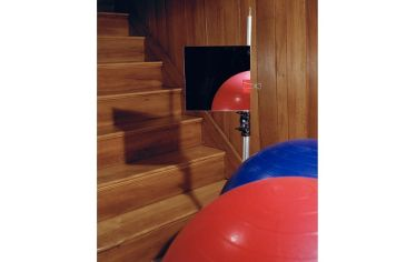 A red sphere and a blue sphere are reflected in a mirror at the base of a wooden staircase.