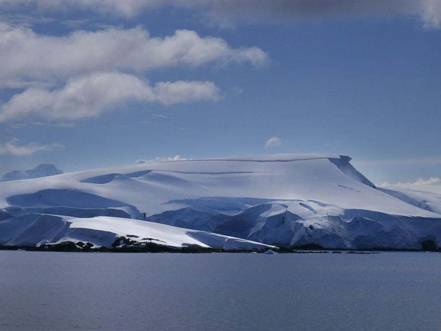Snow covered hill and water in Antarctica