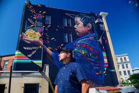 artist standing in front of their large mural of girl holding flowers